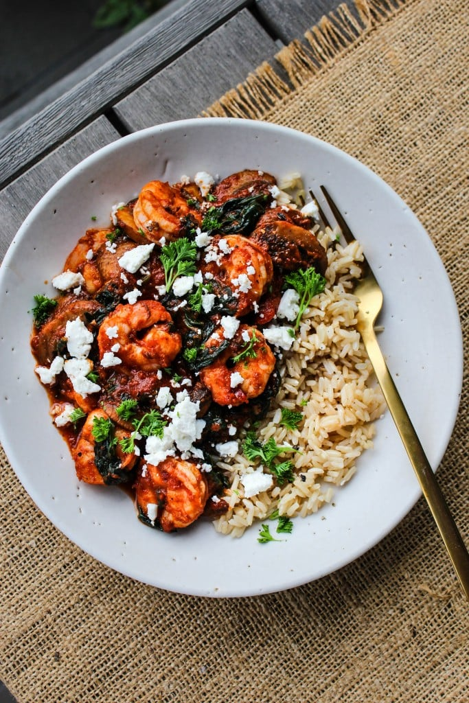 overhead white bowl with sauteed shrimp, tomato sauce,vegetables, feta, parsley over brown rice with gold fork