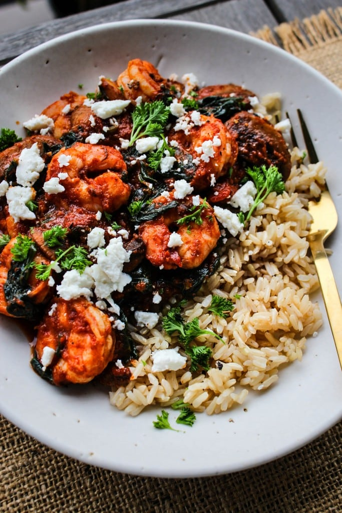 side angle of white bowl with sauteed shrimp, tomato sauce,vegetables, feta, parsley over brown rice with gold fork