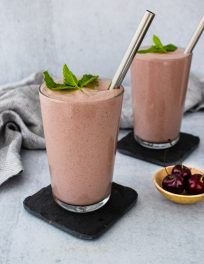 two glasses of cherry yogurt smoothie with mint leaf and straw on top