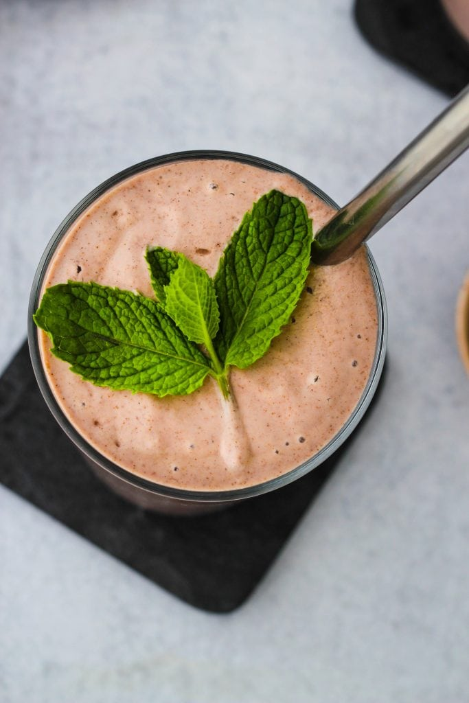overhead shot of glass with cherry smoothie straw and mint leaf