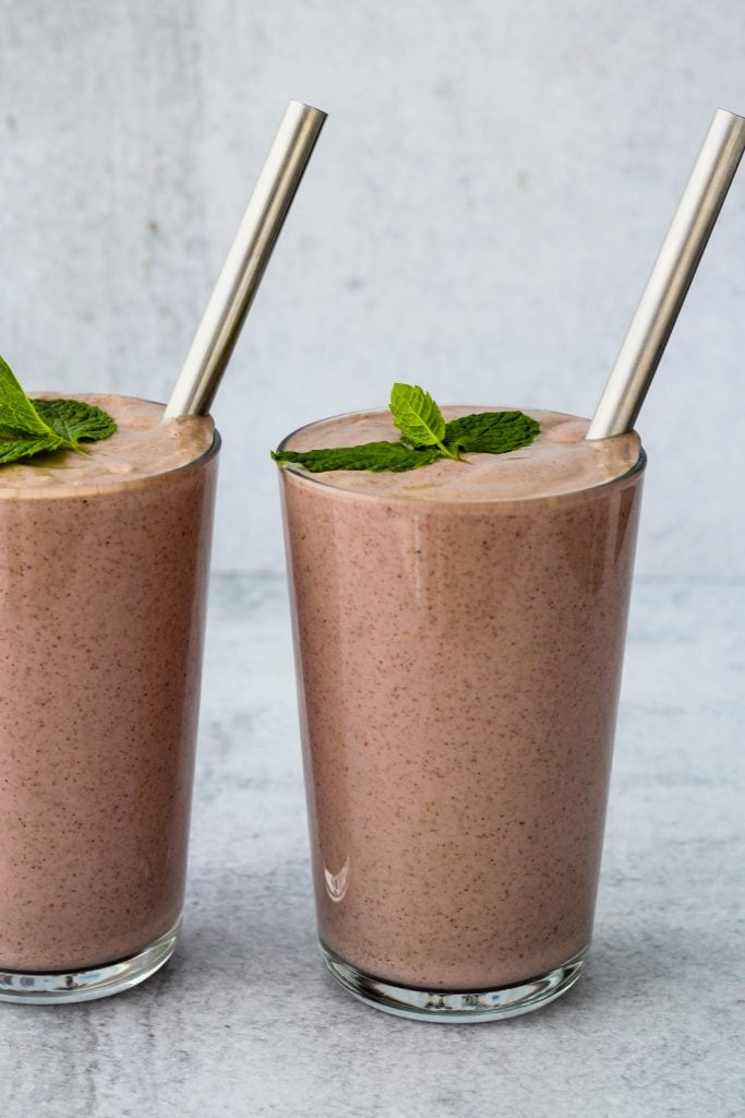 side angle of two glasses of cherry yogurt smoothie with mint leaf and straw on top