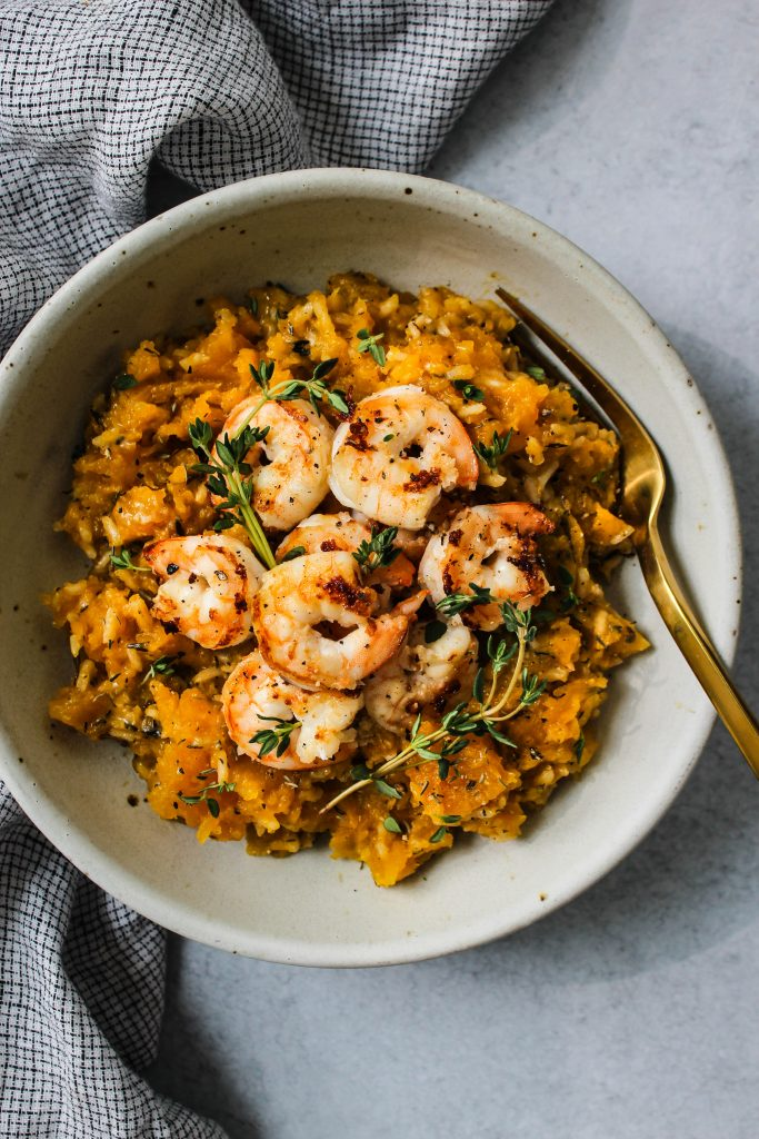 overhead shot of white bowl with butternut squash rice topped with shrimp