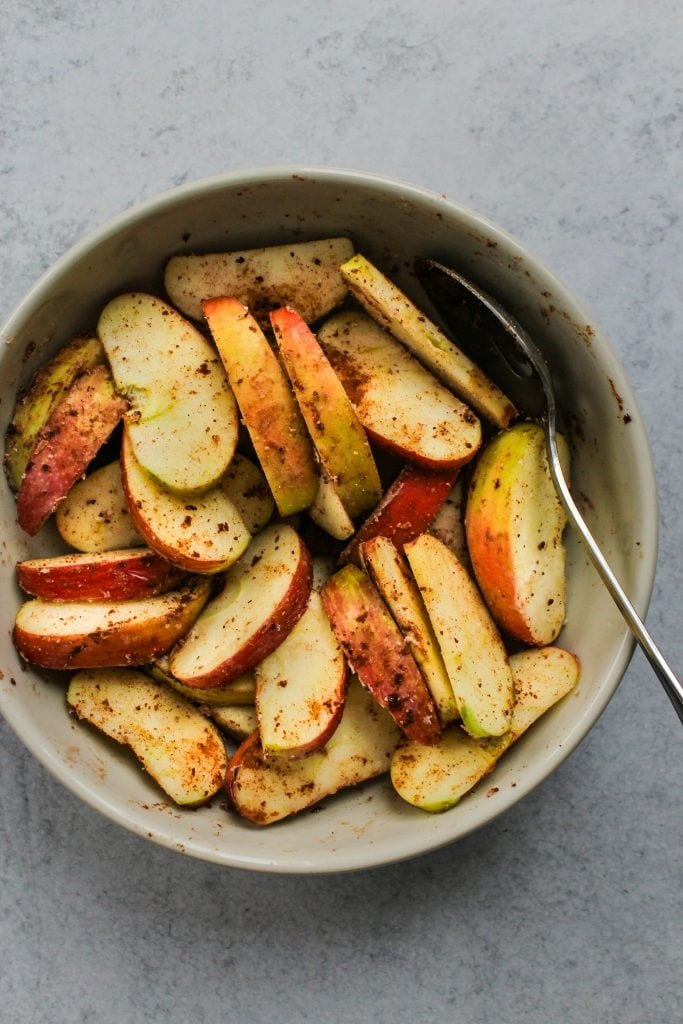 apple slices tossed in cinnamon in white bowl