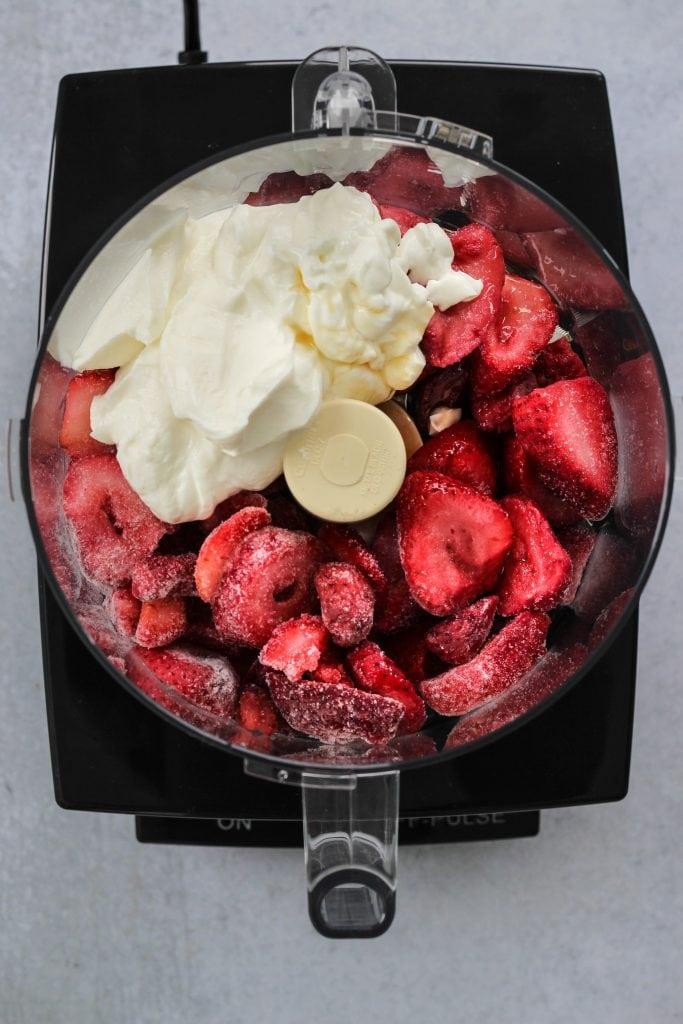 Overhead shot of a food processor with frozen strawberries and greek yogurt inside.