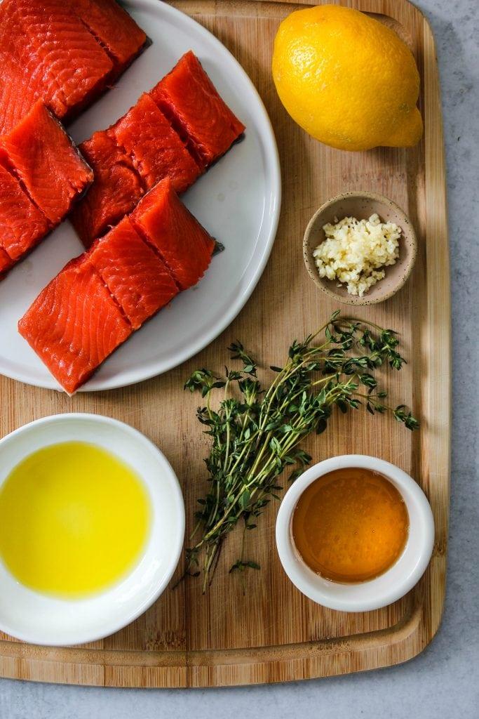 wood cutting board with bowls of honey, olive oil, lemon, garlic, thyme, and salmon on a plate