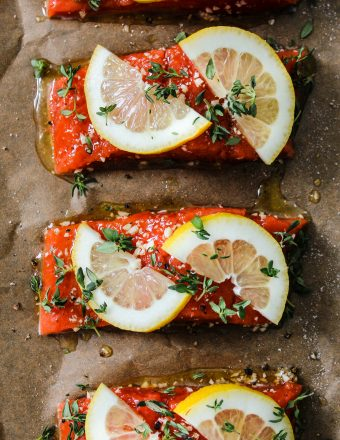 Overhead photo of parchment-lined baking dish with four salmon fillets with lemon and thyme on top.