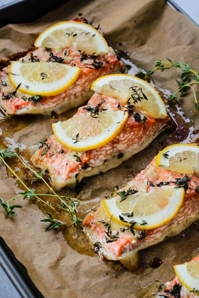side angle shot of parchment-lined baking dish with three pieces of baked salmon fillets with lemon and thymeon top