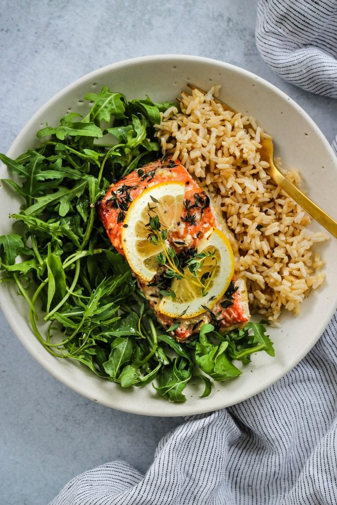 overhead shot of white bowl with arugula, baked honey lemon salmon, and brown rice
