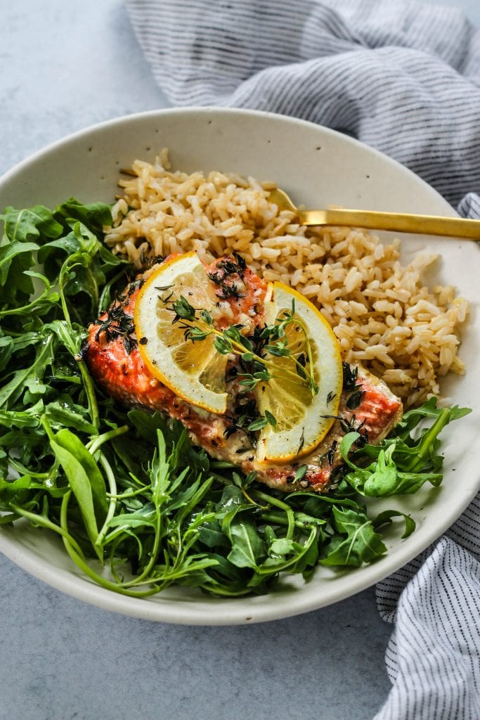 side angle shot of white bowl with arugula, baked honey lemon salmon, and brown rice