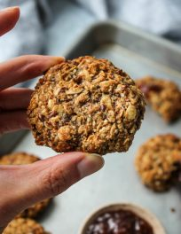 hand holding oatmeal cookie with chia jam