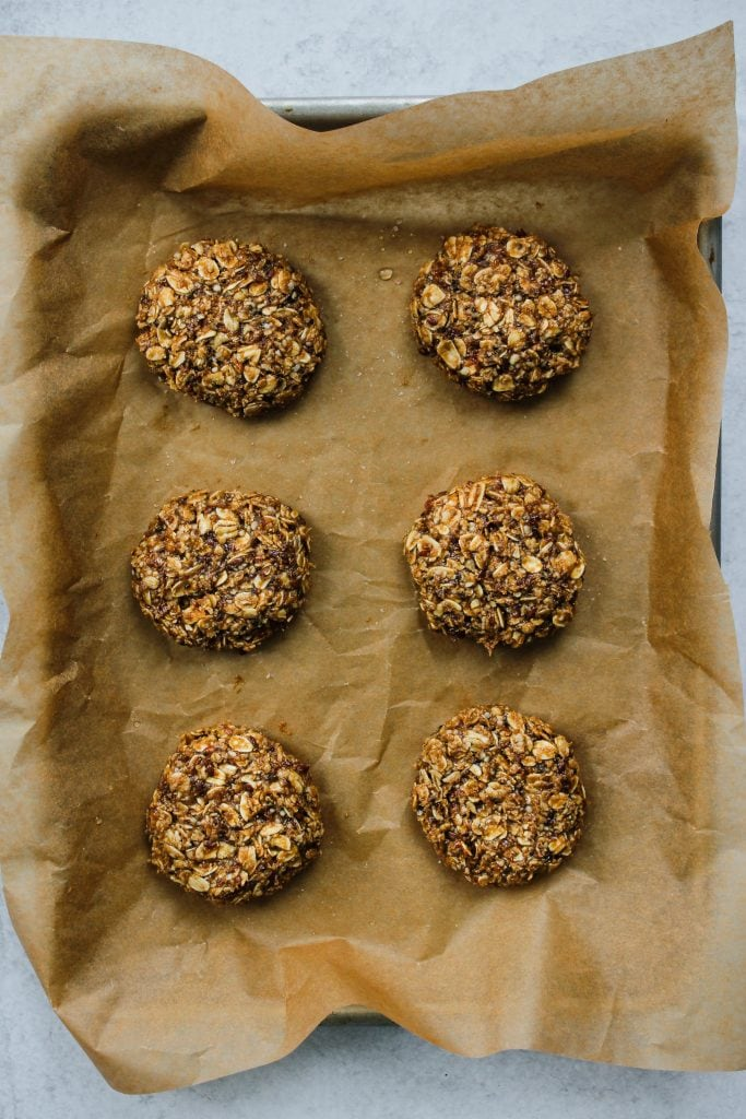 parchment-lined baking sheet with 6 oatmeal cookies