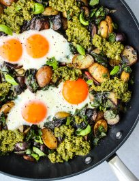 black skillet with pesto potato hash topped with fried eggs