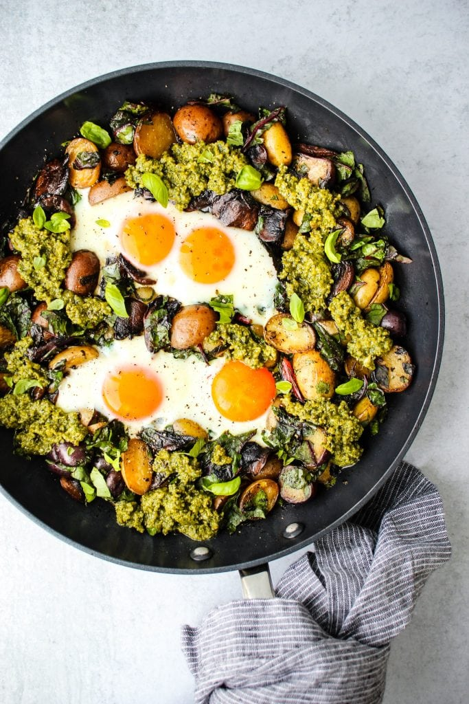 overhead shot of black skillet with pesto potato hash topped with fried eggs