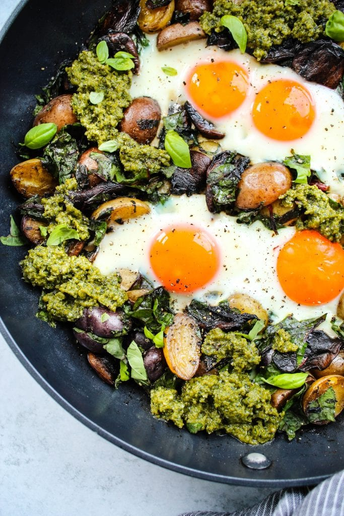 close up shot of black skillet with pesto potato hash topped with fried eggs
