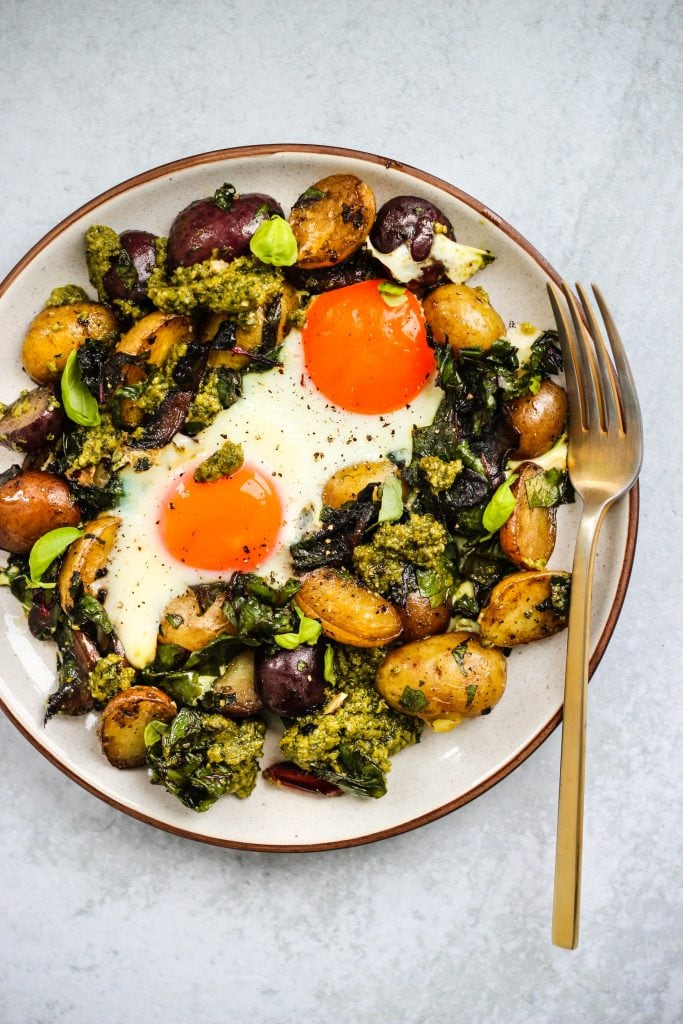 white plate with serving of pesto potato hash and two fried eggs