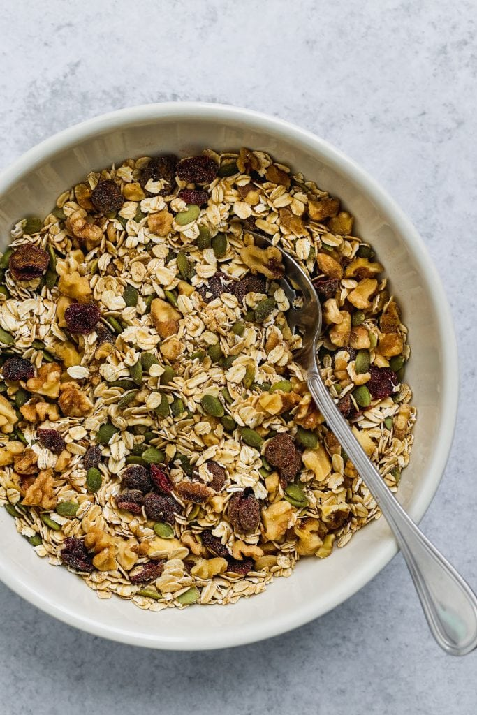 large white bowl with oats, pumpkin seeds, walnuts, and dried cranberries mixed together