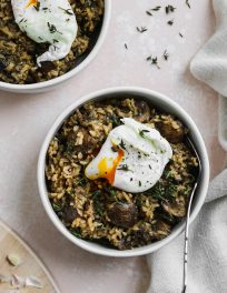 overhead photo of 2 white bowls with miso mushroom rice inside, topped with a poached egg over a light pink backdrop