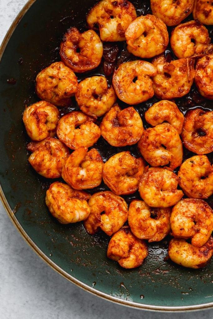 overhead shot of black pan with sautéed shrimp with garlic, paprika, and honey