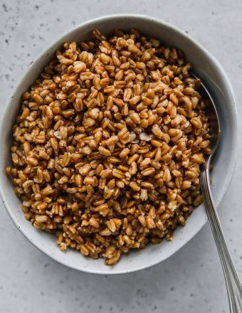 overhead shot of cooked farro in a light blue bowl and a silver spoon
