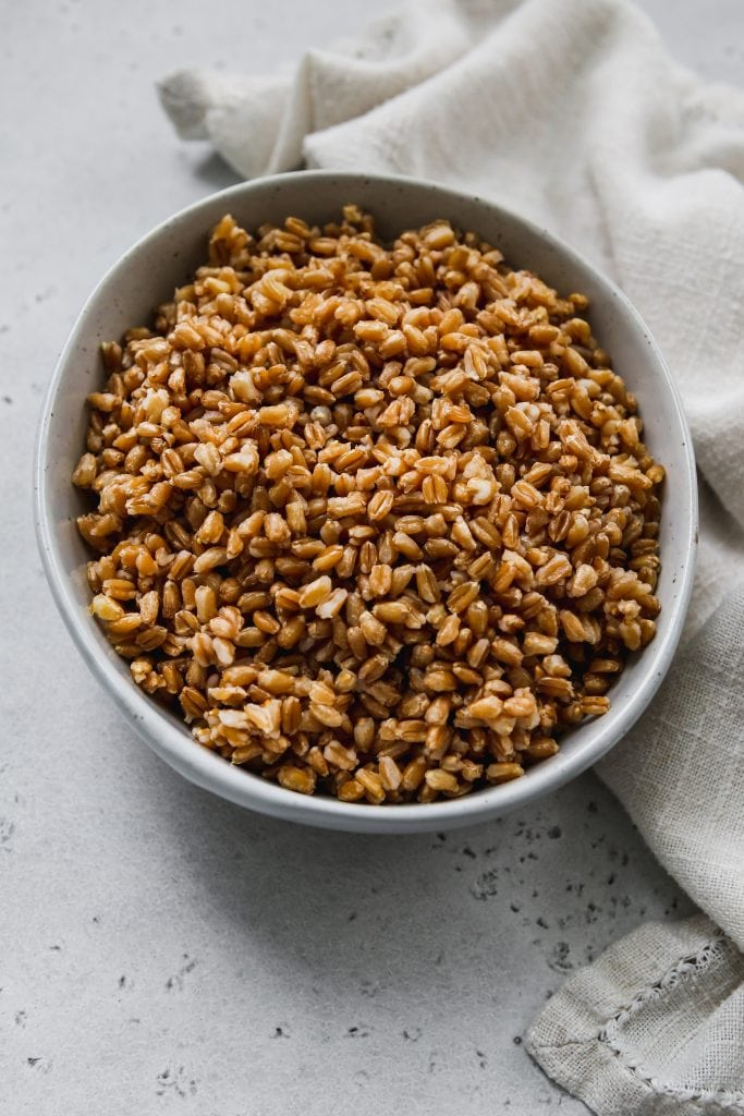 45 degree angle photo of cooked farro in a light blue bowl with a linen napkin
