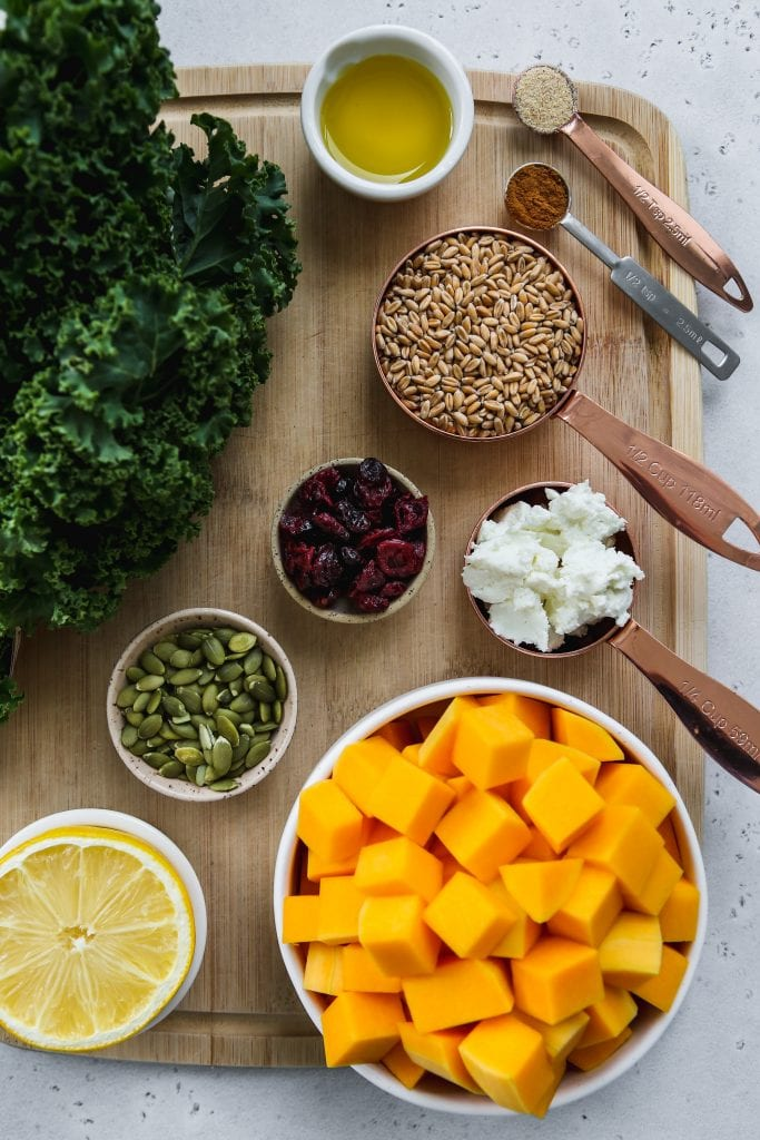 overhead photo of wood cutting board with small bowls of kale butternut squash salad ingredients