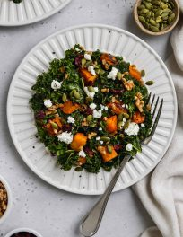 overhead zoomed out photo of kale butternut squash salad with farro and goat cheese on a white plate