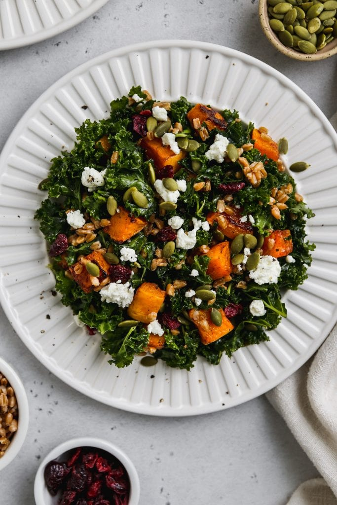 overhead closeup photo of kale butternut squash salad with farro and goat cheese on a white plate