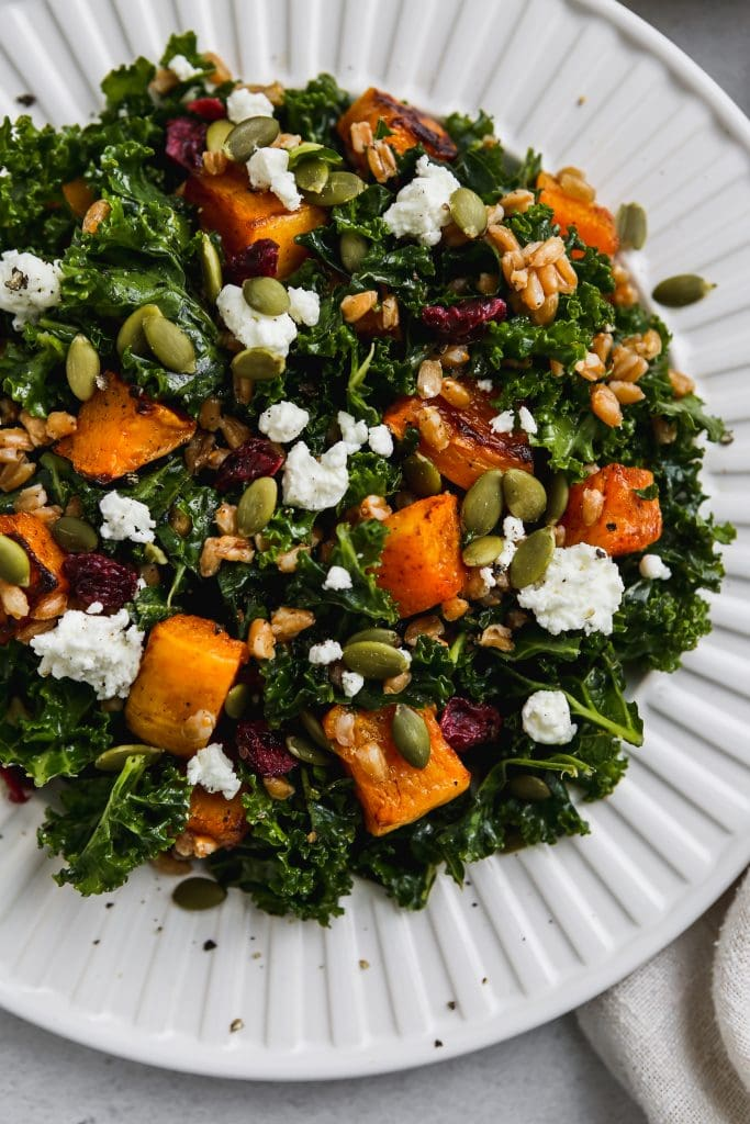 closeup photo of kale butternut squash salad with farro and goat cheese on a white plate