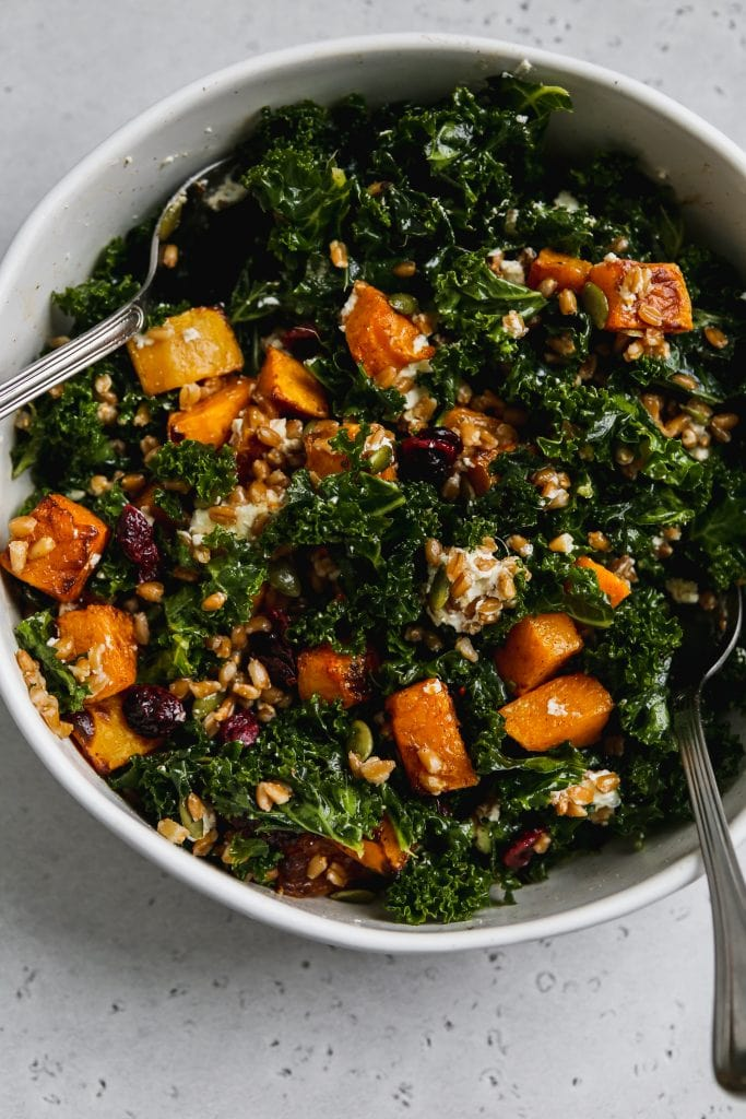 kale butternut squash salad with farro and goat cheese in a large white bowl