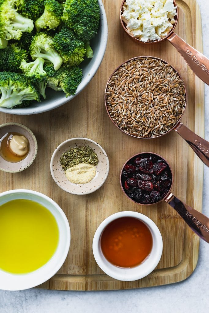 overhead shot of wood cutting board topped with bowls of ingredients for broccoli farro salad
