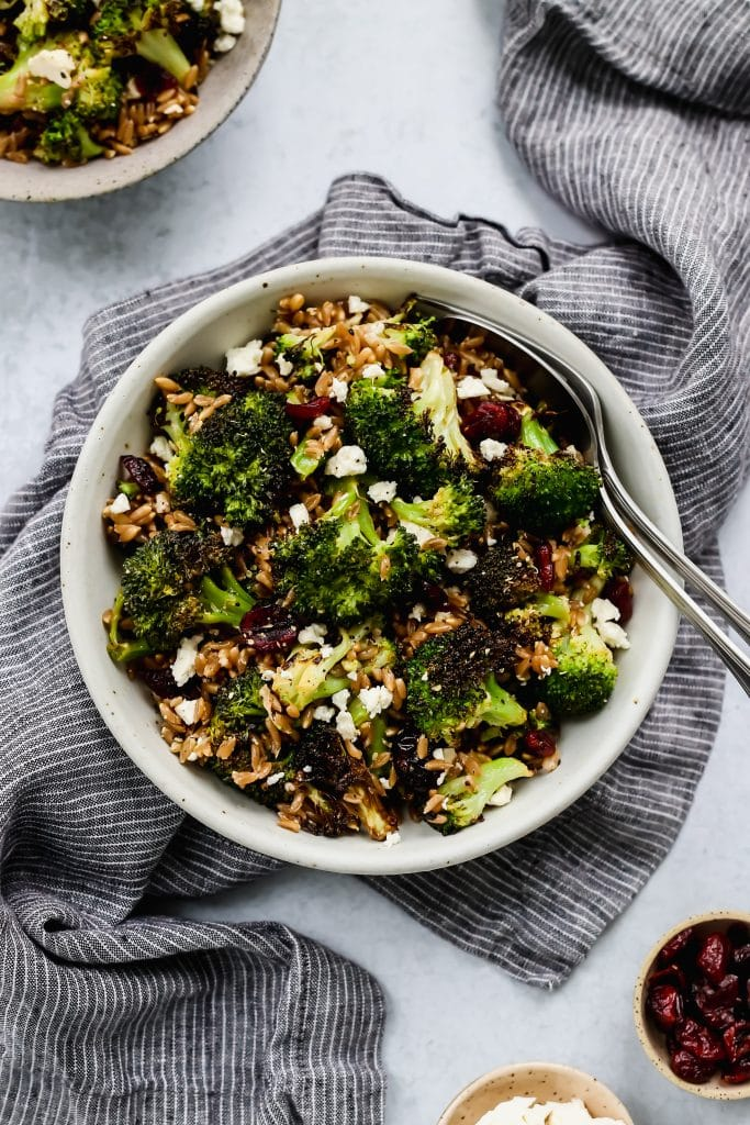 overhead shot of white bowl with roasted broccoli, farro, dried cranberries, and feta salad over blue dish cloth