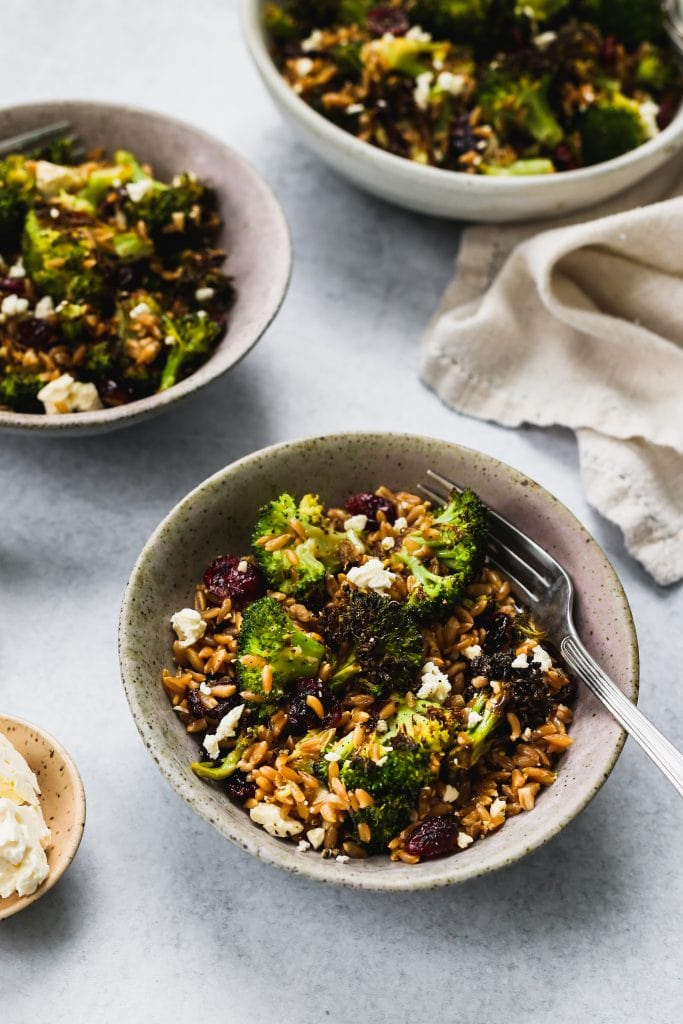 45 degree angle shot of three bowls with roasted broccoli, farro, dried cranberries, and feta salad