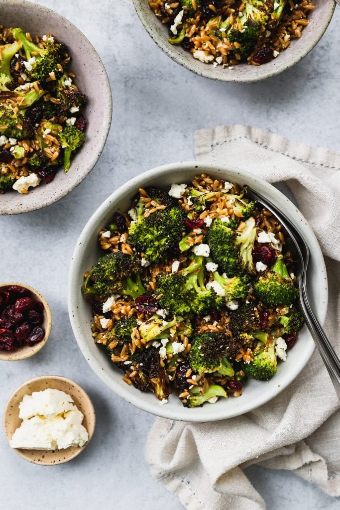 overhead shot of 3 bowl with roasted broccoli, farro, dried cranberries, and feta salad