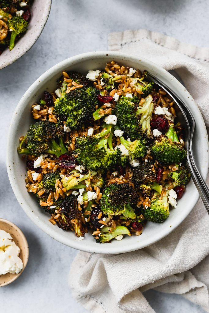 closeup shot of white bowl with roasted broccoli, farro, dried cranberries, and feta salad