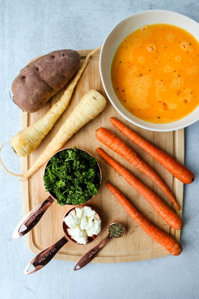 overhead shot of wood cutting board with carrots, parsnips, sweet potatoes, and bowls of ingredients