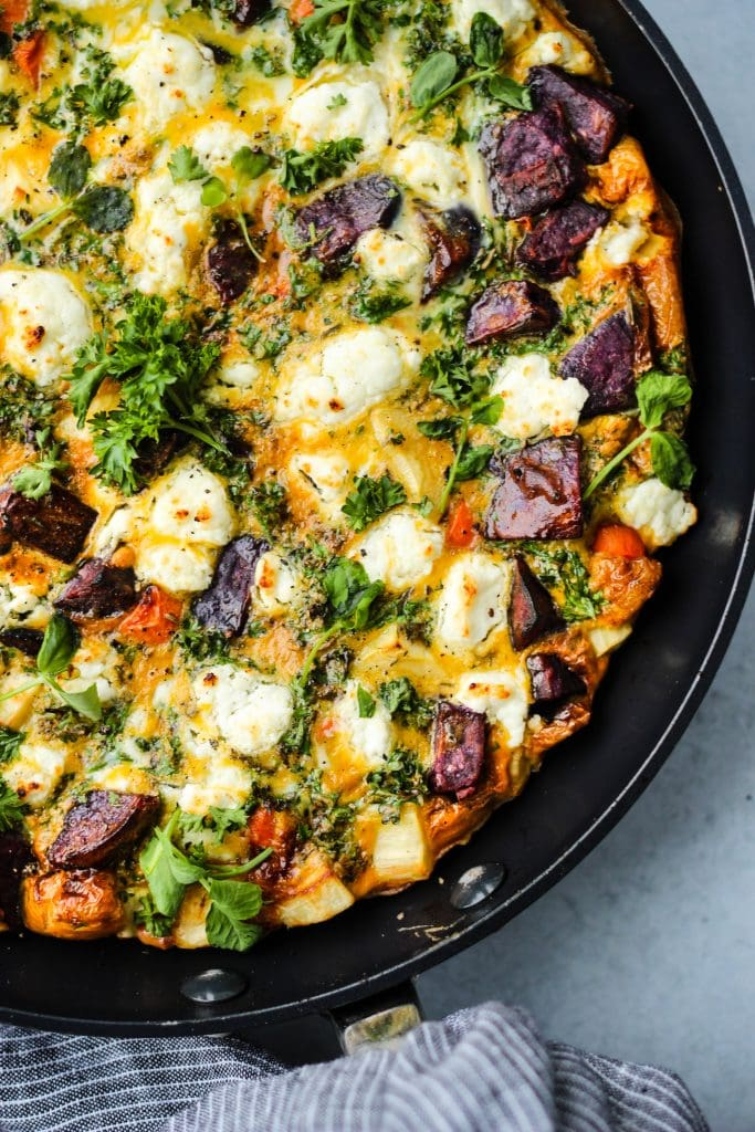 close up shot of black skillet with a root vegetable frittata, goat cheese, and parsley inside