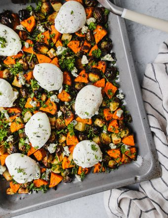 overhead shot of brussels sprouts and sweet potato hash on sheet pan topped with poached eggs