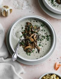 overhead photo of white bowl of vegan cream of mushroom soup with cashews and garlic