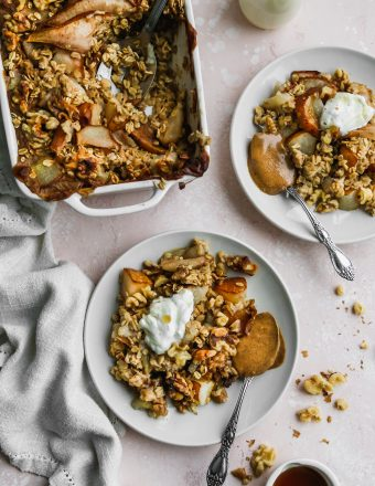 overhead photo of baked pear oatmeal in baking dish with two servings on small white plates on light pink backdrop