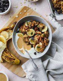 overhead photo of bowl with yogurt, tahini granola, and banana slices