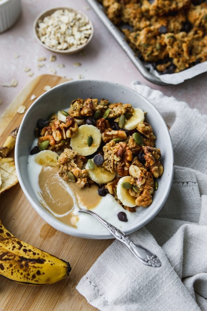 45 degree angle photo of bowl with yogurt, tahini granola, and banana slices