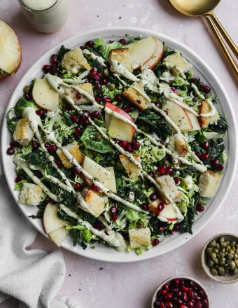 overhead photo of white plate topped with kale brussels sprout salad with apples, pomegranates, and a vegan caesar dressing drizzled on top