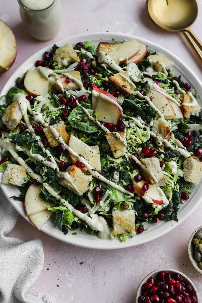 45 degree angle photo of white plate topped with kale brussels sprout salad with apples, pomegranates, and a vegan caesar dressing drizzled on top