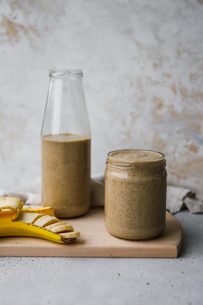 straight on shot of a glass jar and glass bottle filled with chai tea smoothie on a wood cutting board, with a sliced banana for decoration
