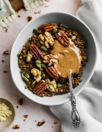 overhead photo of vegan gingerbread steel cut oatmeal light blue bowl topped with almond butter, walnuts, and pecans