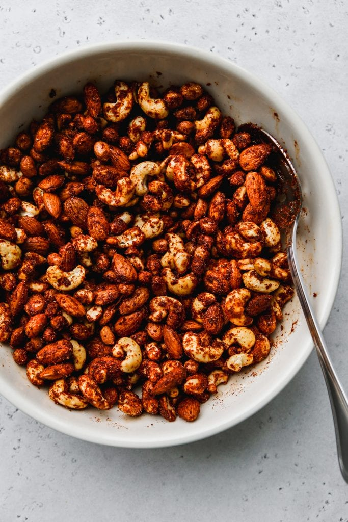 overhead photo of white bowl with raw cashews, almonds, and peanuts stirred together with BBQ spices
