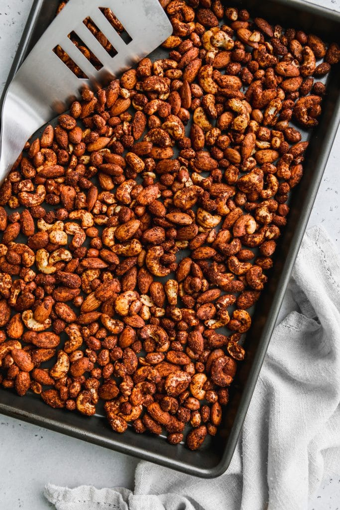 overhead photo of baking sheet topped with BBQ spiced peanuts, almonds, and cashews