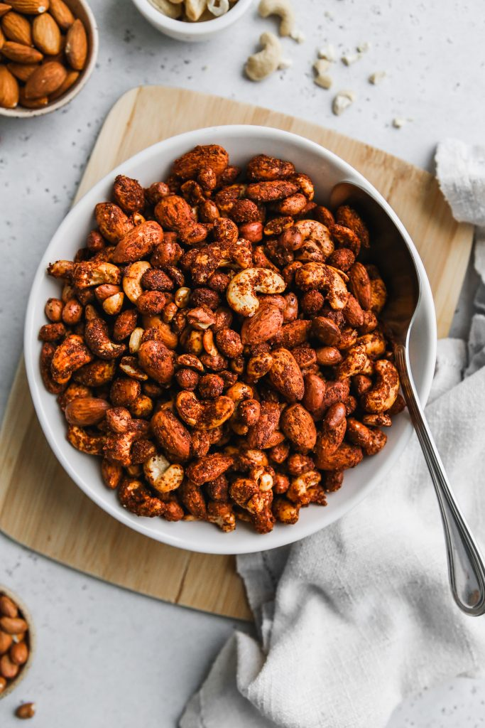 overhead photo of white bowl of savoury spiced nut mix on wood cutting board