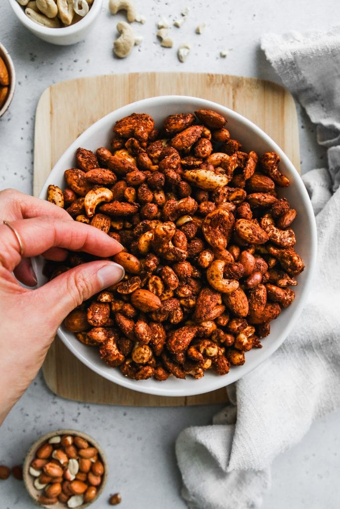 overhead photo of hand grabbing spiced nuts in a whole bowl on top of wood cutting board