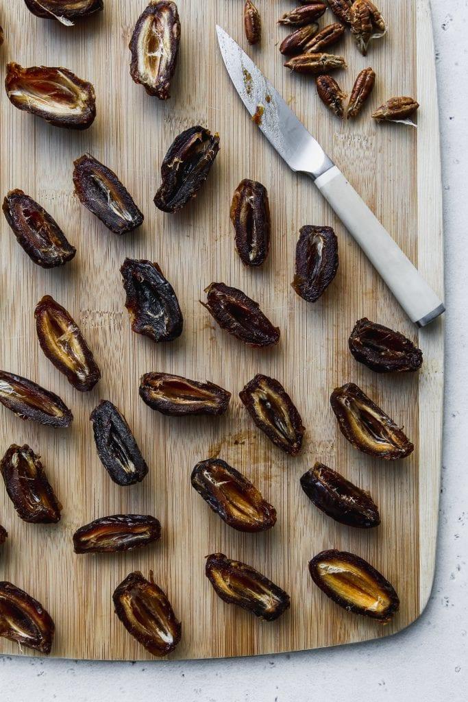 overhead photo of medjool dates cut in half on a wood cutting board